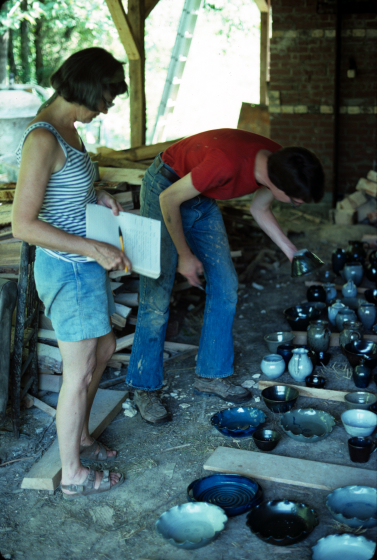 Nancy Sweezy examining pottery being removed from a kiln with apprentice Robert Coombs, Jugtown, North Carolina, ca. late 1970s, courtesy Nancy Sweezy