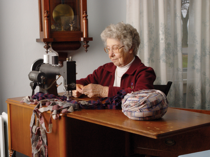 Dorothy Trumpold learned knitting, crocheting and embroidery while growing up in Iowa's Amana Colonies. She began specializing in rugs in the 1940s and continued to weave for more than sixty years. She is pictured here sewing strips of wool and cotton rags together into long strands. East Amana, 2002, photograph by Alan Govenar
