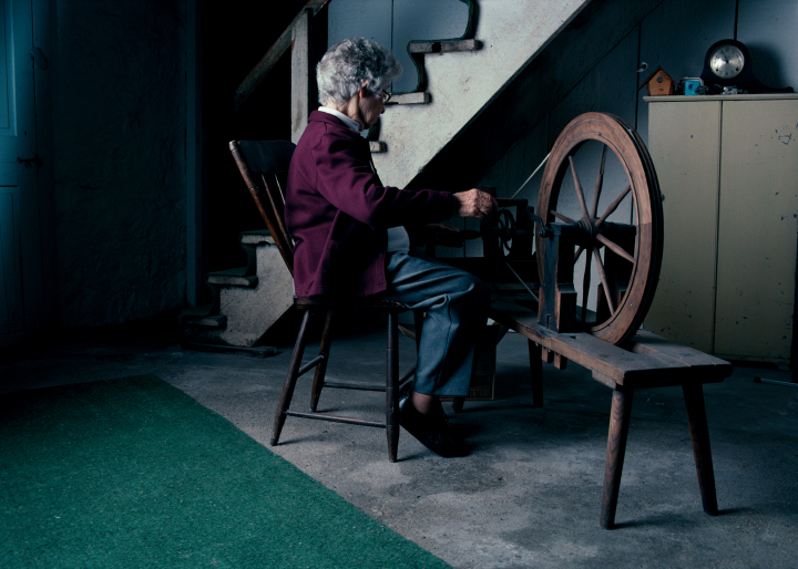 Dorothy Trumpold spinning threads to wind the warp onto the shuttle of the loom, East Amana, 2002, photograph by Alan Govenar